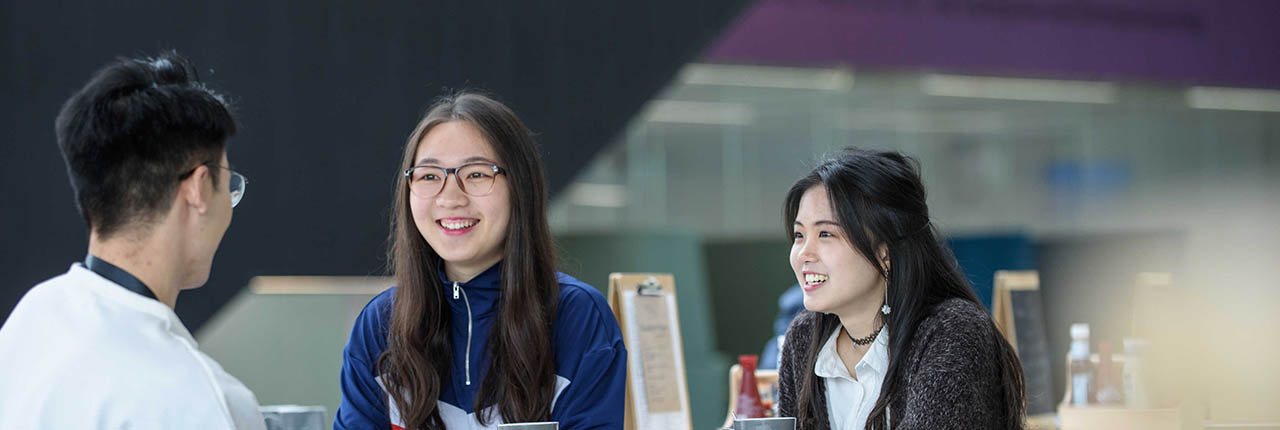 International students talking in a cafe space