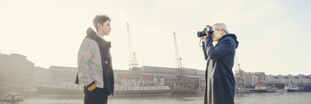 Student taking photograph of model on Bristol Harbourside
