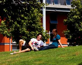 Two UWE students sitting on a lawn