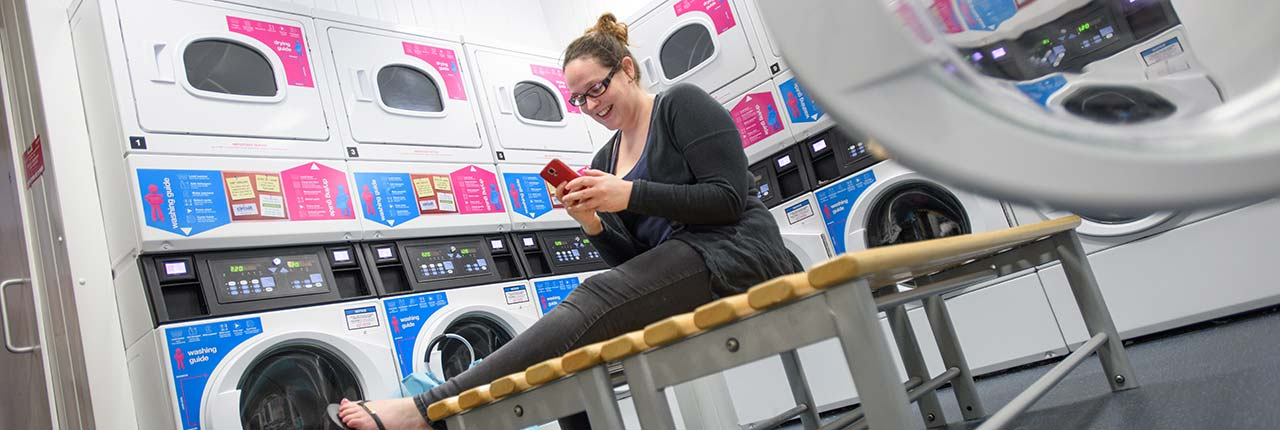 Student in laundry looking at her phone
