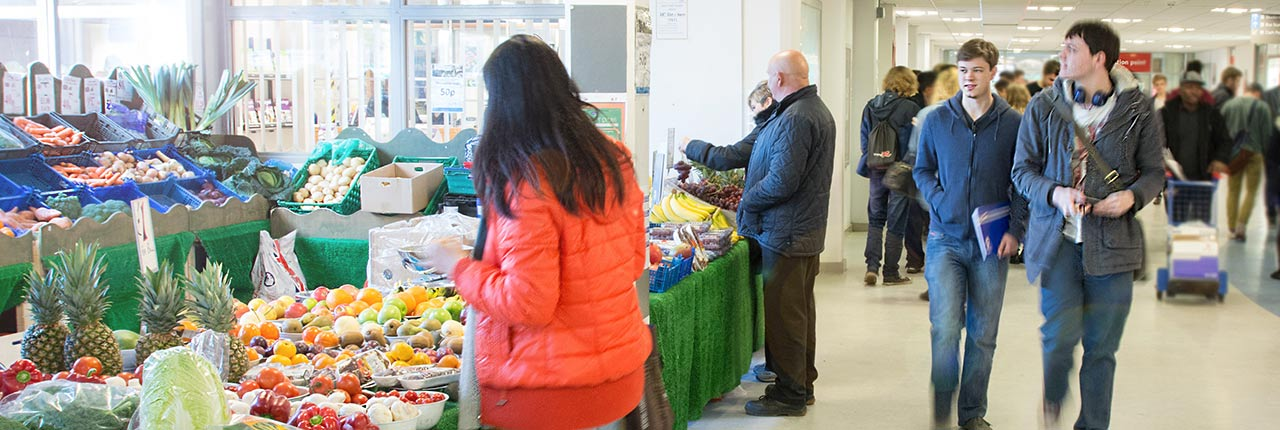 Student buying produce at the University's fruit and vegetable stall