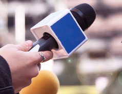 Journalist holding a microphone while interviewing