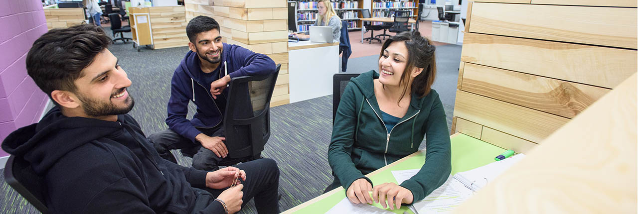 Three students having a conversation in a library