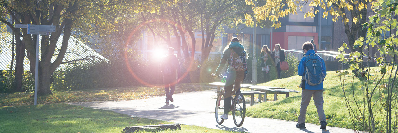 Students walking and cycling on campus