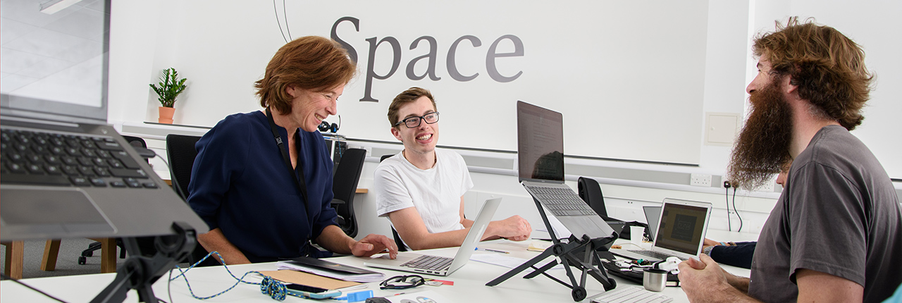 Launch Space residents using laptops at a co-working table