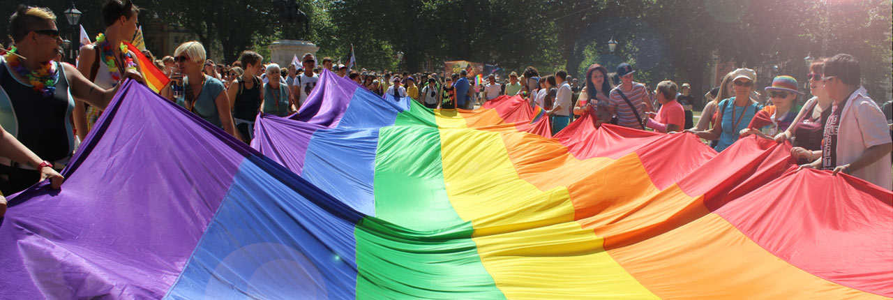 A huge LGBT rainbow flag being held by people attending Bristol Pride event