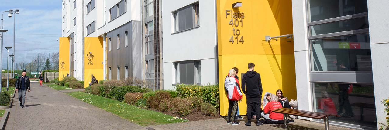 Group of students sitting outside their accommodation in the sun