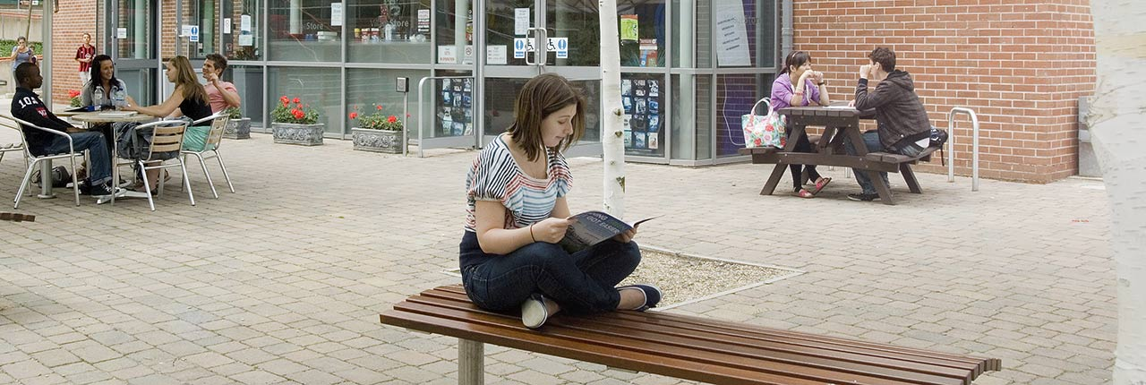 Student sat on a bench reading