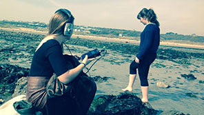 two students at the beach, one is recording sound.