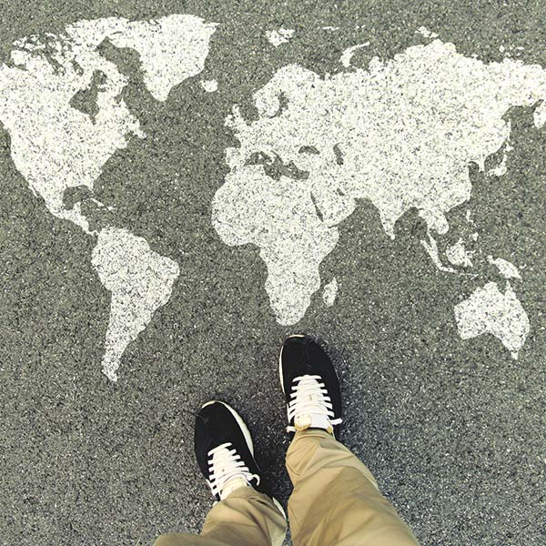 Shoes stepping on to a world map