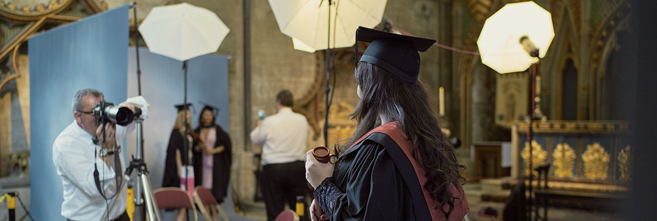 Student having their photo taken on their graduation while wearing robes