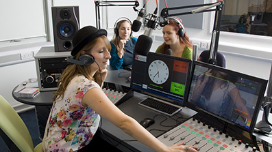 Students broadcasting in a radio studio while another uses audio production equipment