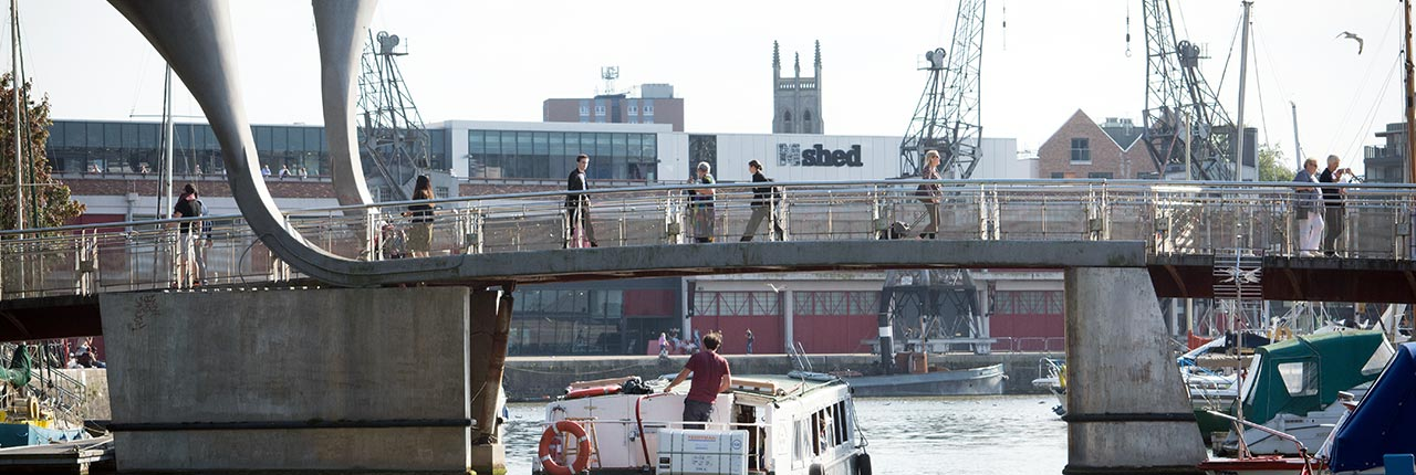 People crossing the bridge at Bristol's harbourside