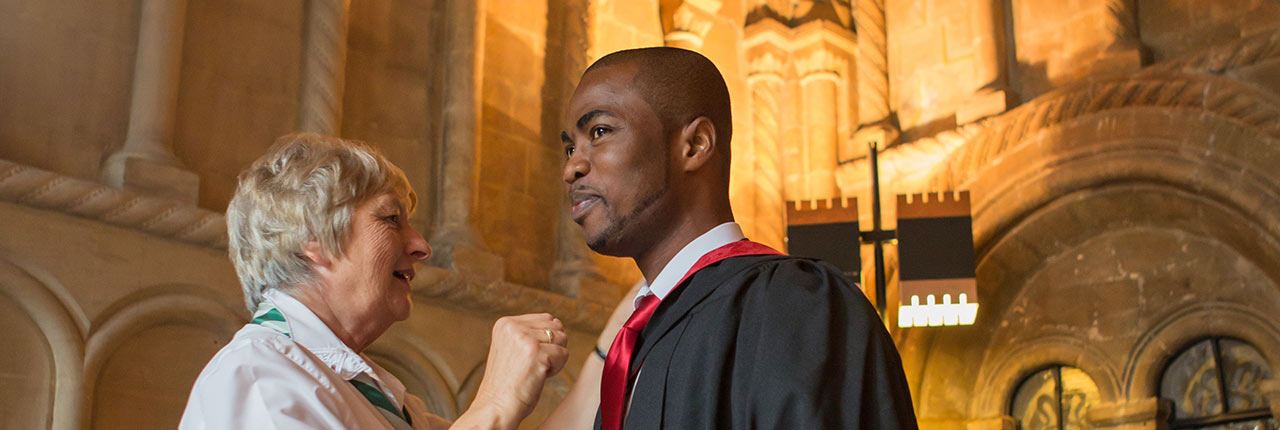 A graduand having his robe fitted in the Cathedral