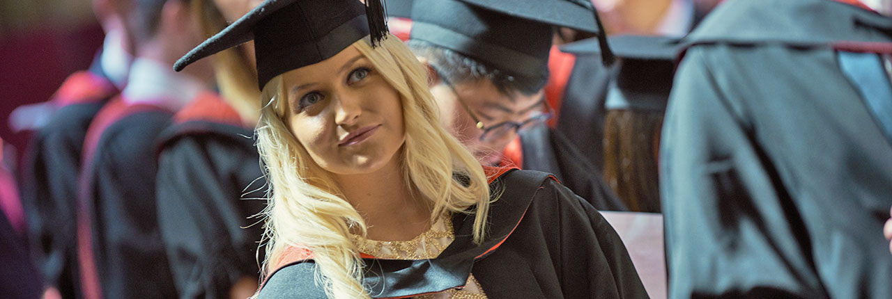 Student pictured in the crowd wearing her graduation gown and cap