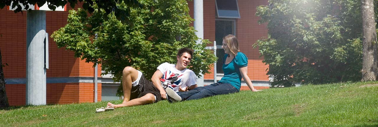 Students sitting on the grass in front of the Student Village