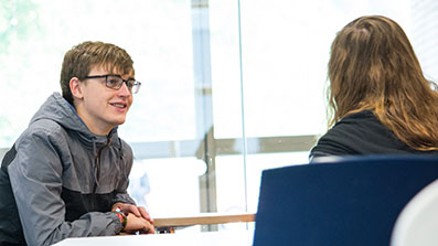 Student having a discussion with a mentor in a glass-fronted meeting room