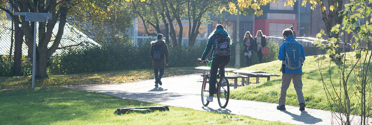Student riding a bike on the Frenchay campus