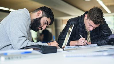 Two students studying with pen, paper and a laptop