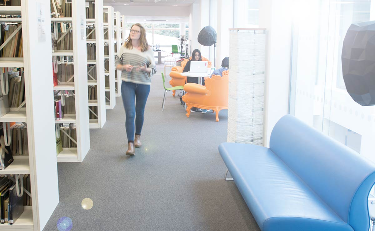 Female students walking through the library