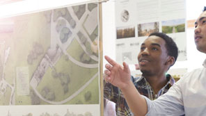 Two urban planning students looking at plans on a wall