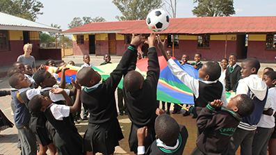 A volunteer student in Africa playing a parashute-and-football game with a class of schoolchildren